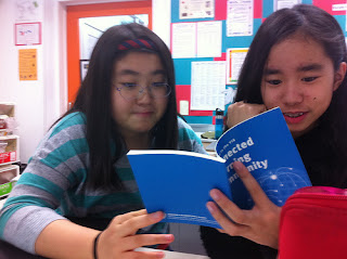 two girls reading a book about connected learning communities