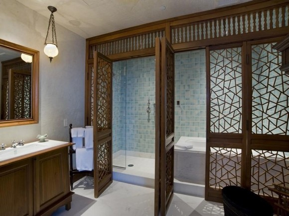 Photo of bathroom with the shower cabin and bathtub separated with wooden doors