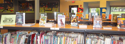 Books arranged upright with covers facing forward on a shelf-top display next to green sign proclaiming 'Oregon Battle of the Books.'  Titles with author names to come.