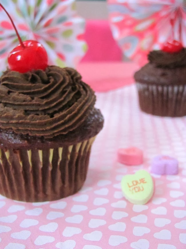 chocolate cupcake with chocolate frosting and a cherry