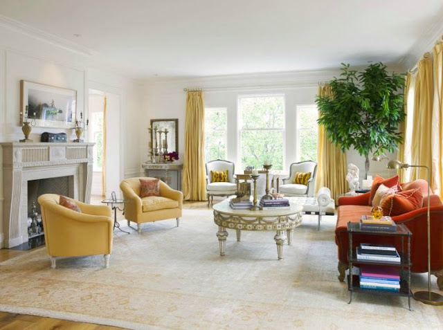 Living room in a san francisco mansion with a molded fireplace, wood floor, a large area rug, a burnt orange sofa, yellow armchairs, a french coffee table, floor length yellow curtains cover the large windows surrounding the room