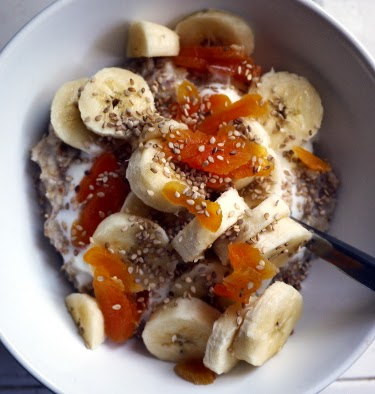 almond flaxseed oatmeal with bananas, yogurt, dried apricots, and sesame seeds