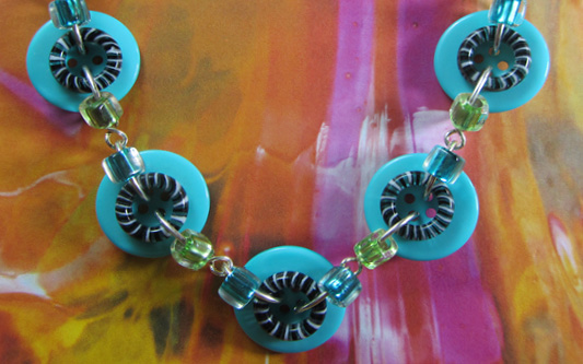 Bold button necklace has big teal buttons with black donut beads and small green and teal beads