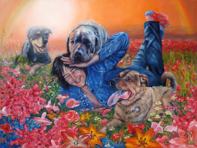 happy woman with her 3 dogs all around her ina field of flowers with rainbow