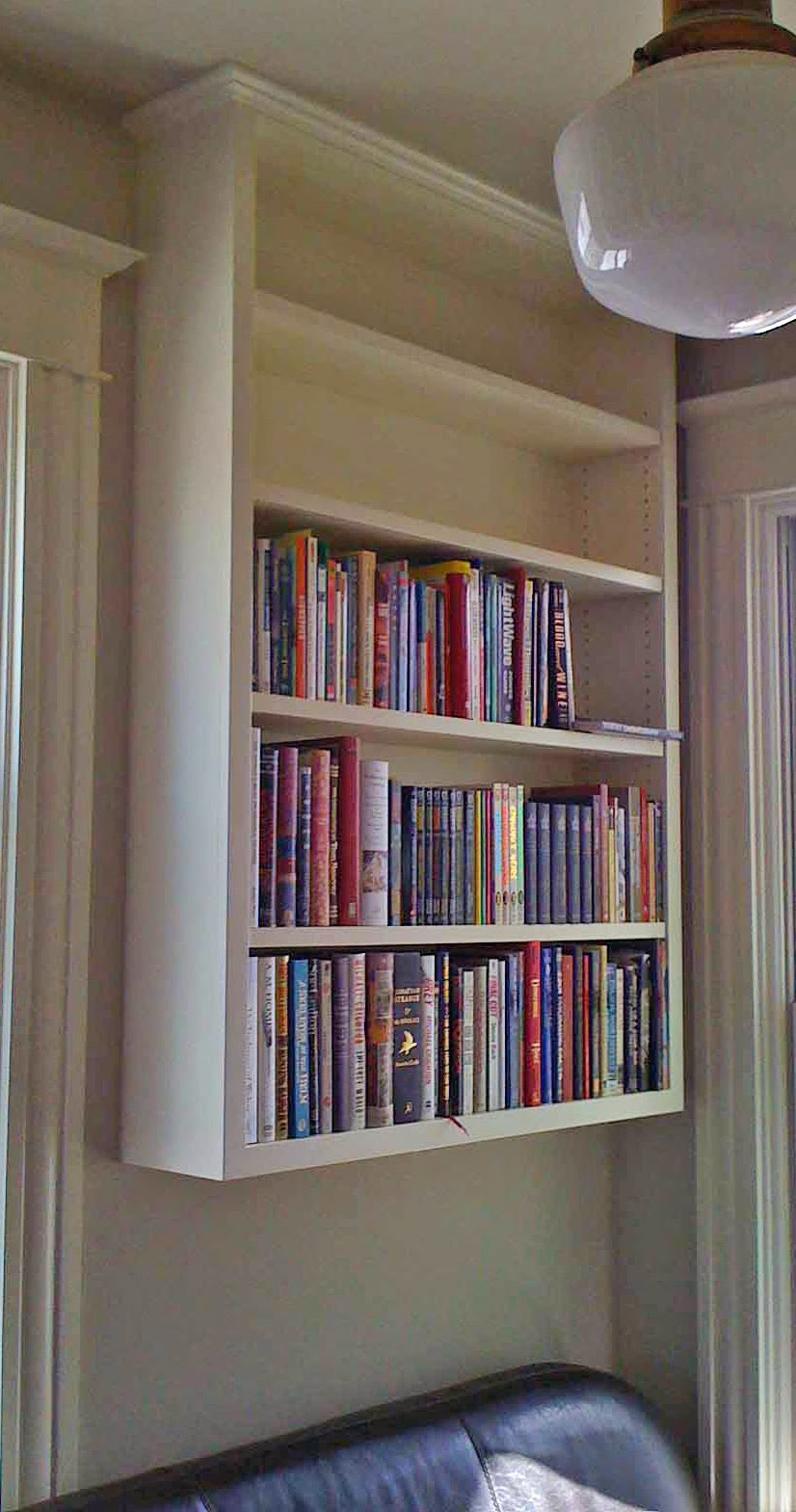 344 Small bookcase hanging on wall and flush with ceiling has adjustable shelves