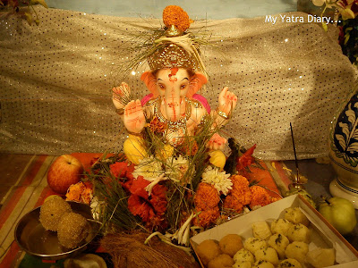 Ganpati idol with modaks and ladoos and flowers