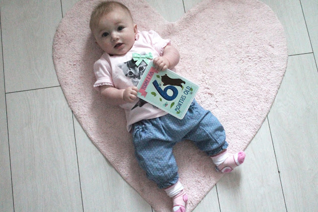 baby lying on pink heart rug holding milestone card today I am 6 months old wearing pink cat tee and jeans