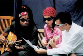 Tribalistas: Carlinhos Brown, Marisa Monte e Arnaldo Antunes. Carlinhos Brown tocando violão.