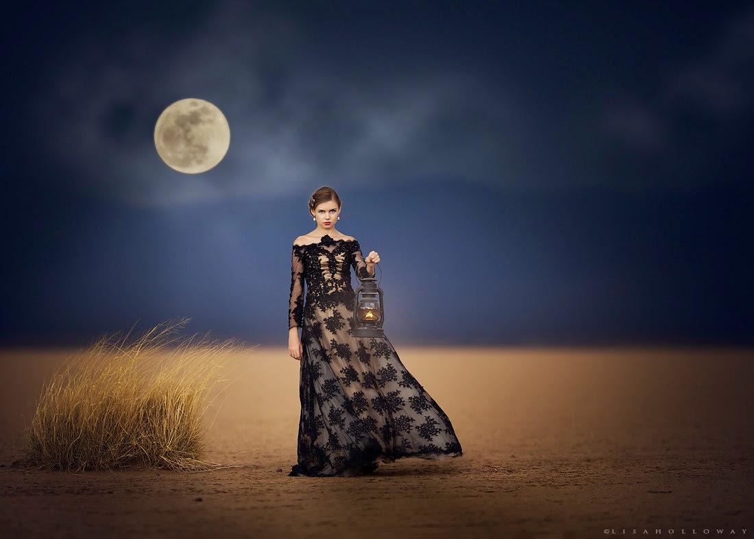 photo de Lisa Holloway représentant une jeune femme en robe en dentelle noire tenant un lampe dans un desert