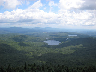 A photo showing tree-covered mountains and blue lakes, as seen from the top of Bald Mountain, Vermont.