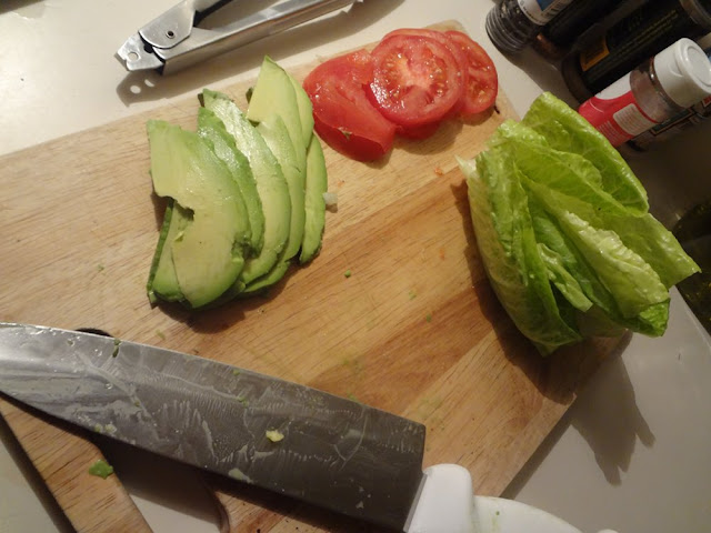 avocado, tomatoes and romaine lettuce on a cutting board