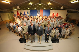 98 new U.S. citizens after their naturalization ceremony in Kandahar, Afghanistan with U.S. Army Maj. Gen. James L. Terry; Karl W. Eikenberry, U.S. Ambassador to Afghanistan; Congressman Darrell Issa; and Robert Looney, USCIS Bangkok District Director. (Photo courtesy U.S. Air Force.)