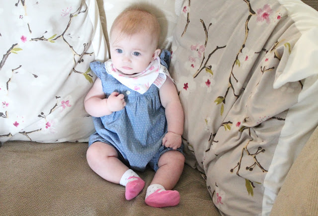 baby girl wearing blue romper with white polka dot and white and pink shoe socks