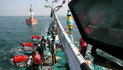 Sejumlah anak buah kapal memindahkan jaring ke atas kapal sebelum ...