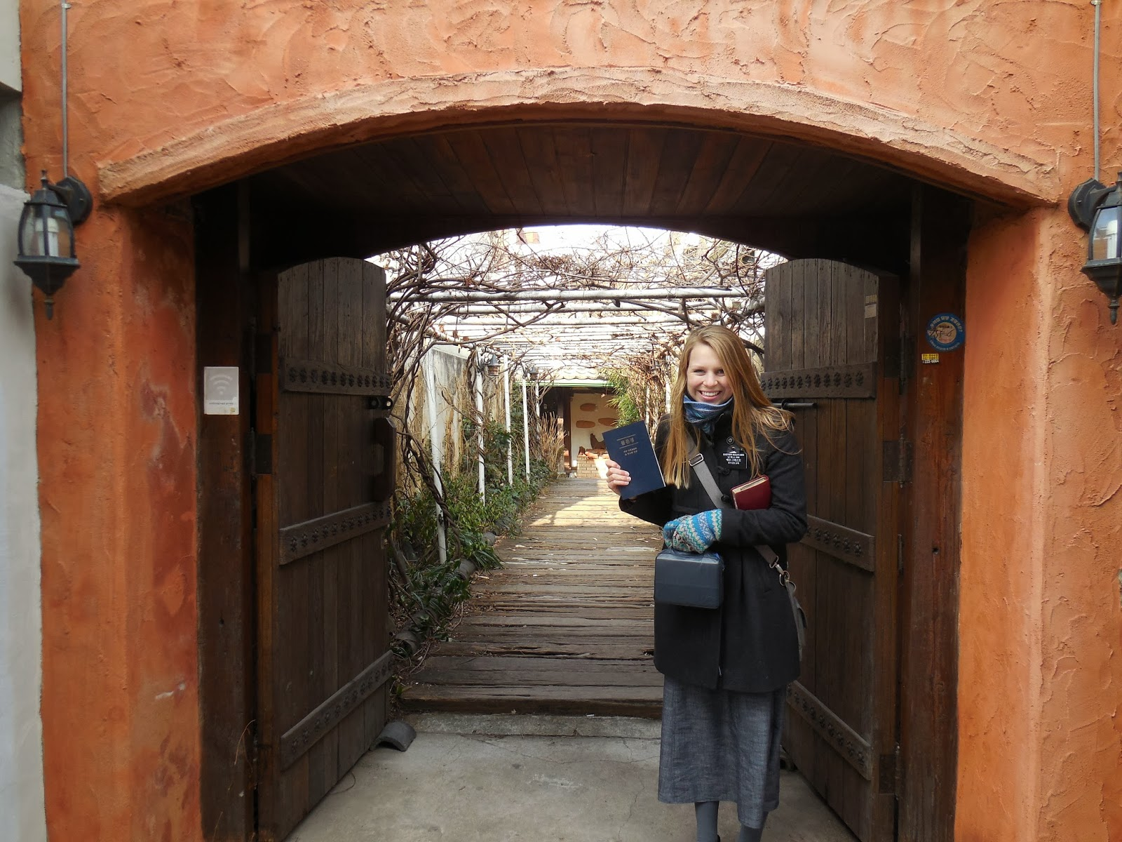 me in front of a cool house (with my korean scriptures and english ones) (quite the armful!)