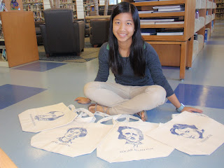 A photo of Yunhan sitting with her totes in front of her.