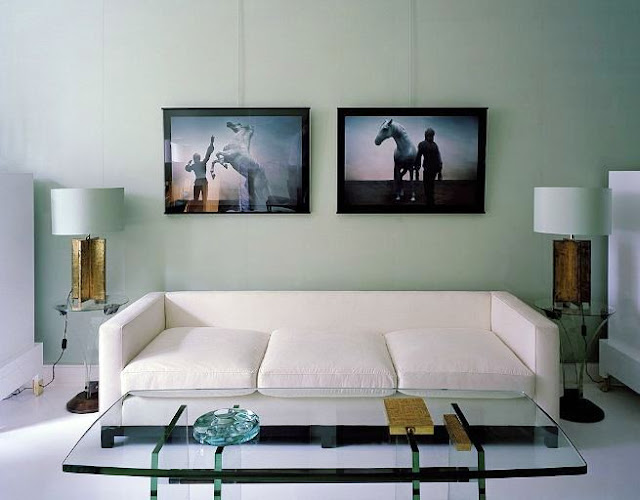 Den with sea foam walls, white sofa, glass coffee table and two pictures of a man with horses above the sofa