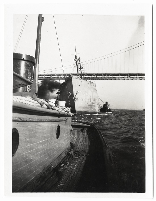 Black-and-white photographic print, 3.5 x 4.25 inches. Looking fore to aft along the deck of one tug, the photograph is of another tugboat alongside a listing vessel that has smoke rolling off the starboard deck. The San Francisco-Oakland Bay Bridge is in the background. Circa 1940s-1950s