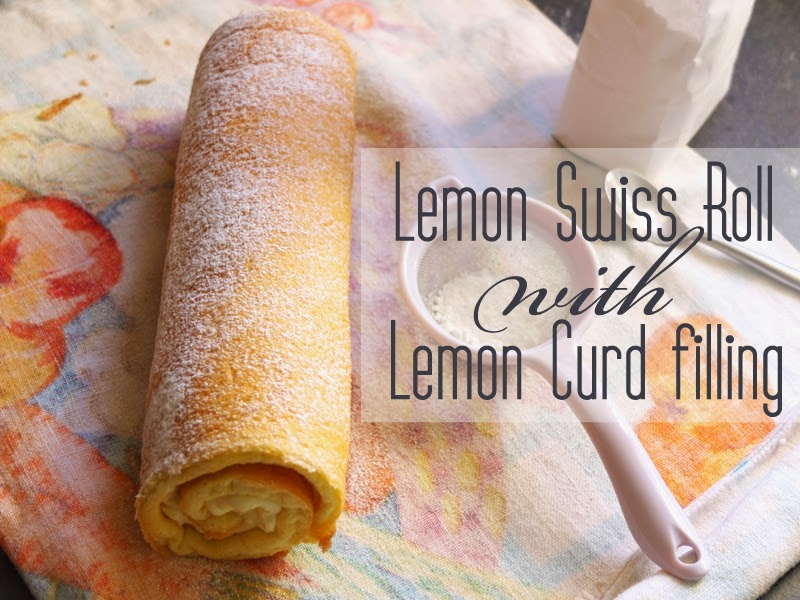 Lemon swiss roll on a tea towel dusted with icing sugar.