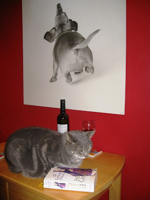 Cat on table with book and wine glass