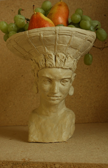 art, sculpture, sarah myers, stoneware, ceramic, escultura, arte, ceramica, fruit, centerpiece, centrepiece, arrangement, figurative, head, woman, basket, bearer, graceful, tranquil, beautiful, food, abundance, plenty, table, face, human, classic, front
