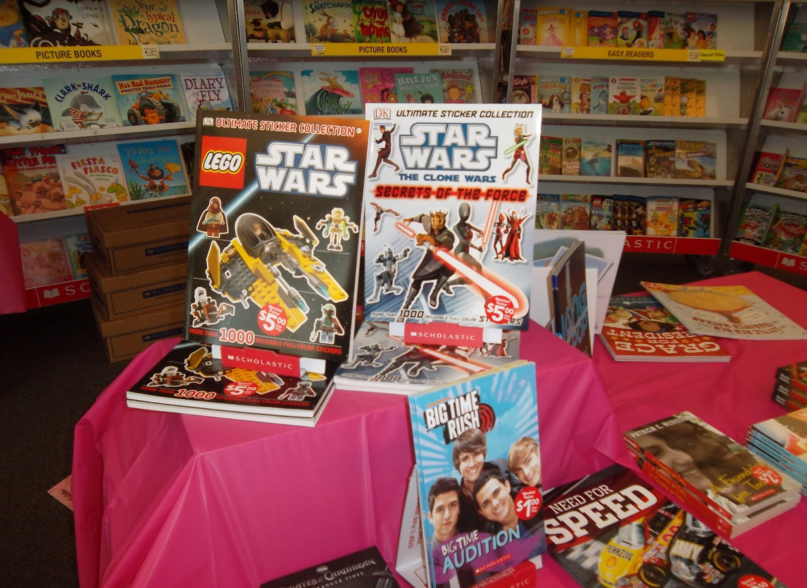 Books put out on a table-top display for a Scholastic Book Fair. Additional books are arranged face-out on shelves in the background.