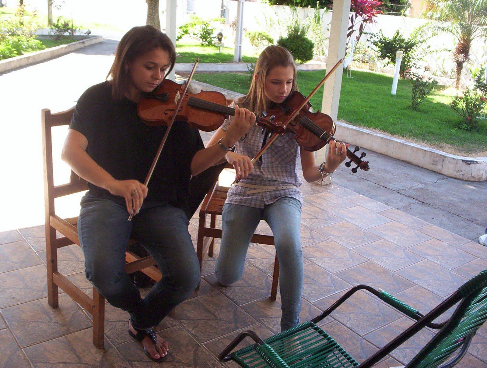 Alunas tocando violino.