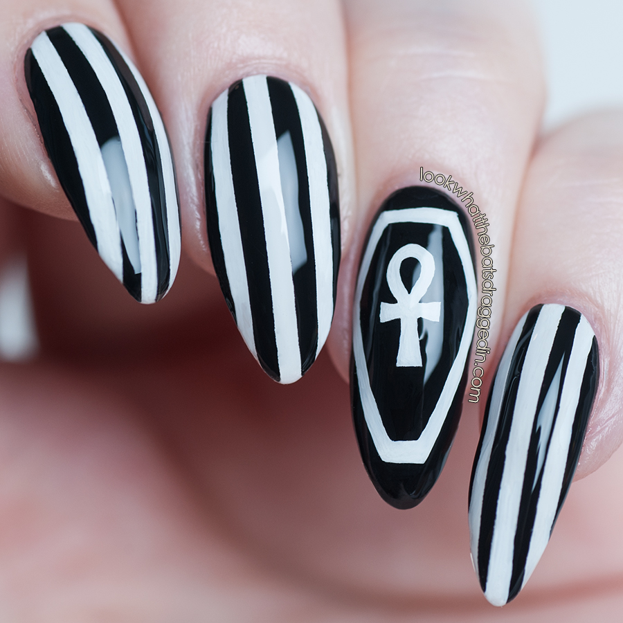 Halloween nail art with a coffin, ankh and striped design.