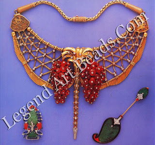 """Top, a ruby bead and diamond 18 kt. gold bib necklace with (WA Indian motifs (enamel on reverse) with a palm tree ornament suspending two bunches of ruby beads (Paris 1949). The """"tree of life"""" platinum brooch with two birds is made of carved emeralds, rubies, cabochon sapphires and diamonds (Paris 1927). The """"Kashmir palm"""" jabot pin, with carved jade, rubies and diamonds, is a classical Moghul design reinterpreted by Cartier Paris and made by the Renault workshop in 1925."""