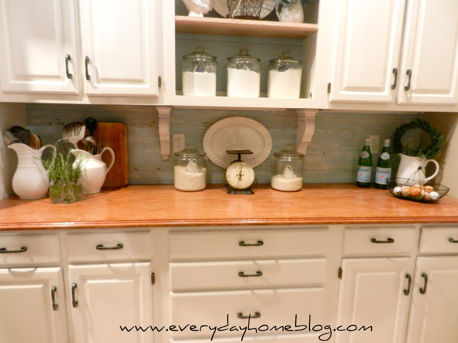 White kitchen white cabinets corbels faux backsplash brick paint