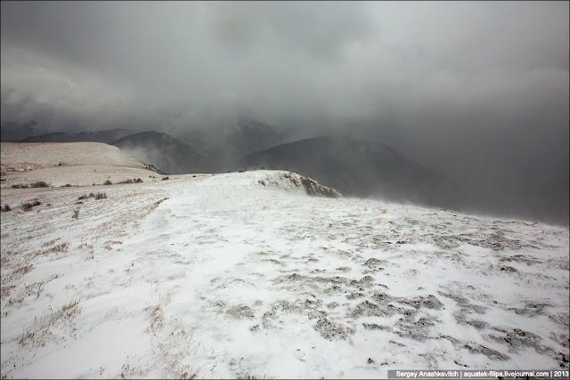 Смена картинки и окружающей среды произошла мгновенно, как только мы поднялись на открытое пространство с крутого склона, по которому поднимались. Теперь понятно, почему там было тихо. Он служил естественным щитом от той непогоды, которая творилась наверху... Метель, колючий противный снег и резко понижающаяся температура.