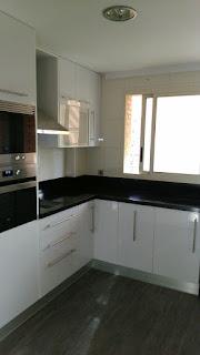 Puertas de cocina blanca con granito negro intenso.