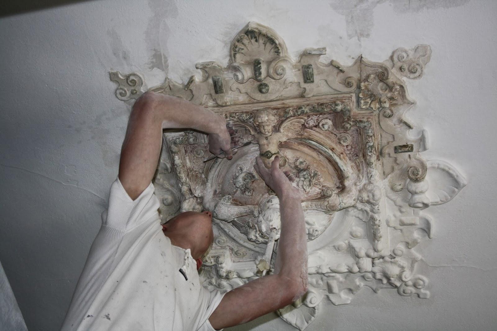 Das Bild zeigt eine Stuckrosette aus der Gründerzeit die von alten Farbschichten befreit wird.