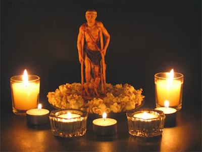 La imagen de San Lázaro sobre un plato con palomitas de maiz y velas encendidas