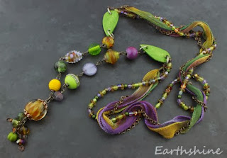 http://earthshine.indiemade.com/product/purple-green-and-gold-mixed-media-artisan-necklace?tid=1