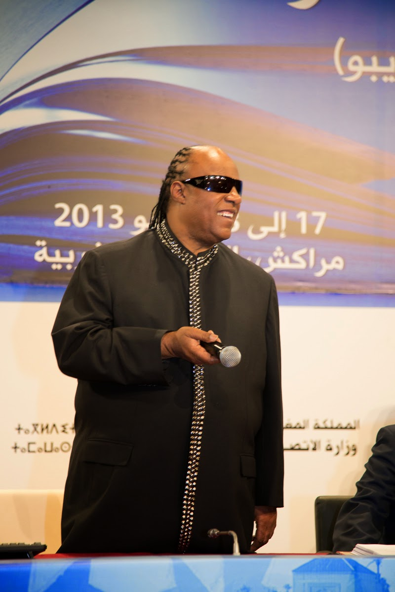 Stevie Wonder standing holding a microphone, smiling