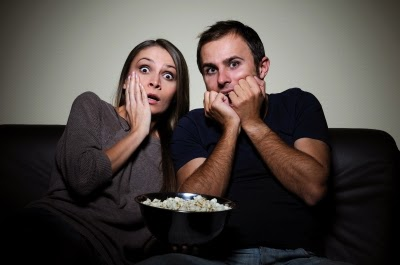 man and woman watching scary show on tv