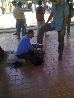 Shoe shine man polishing man's shoes at railway station, andheri bandra cst central railway, shoe polisher