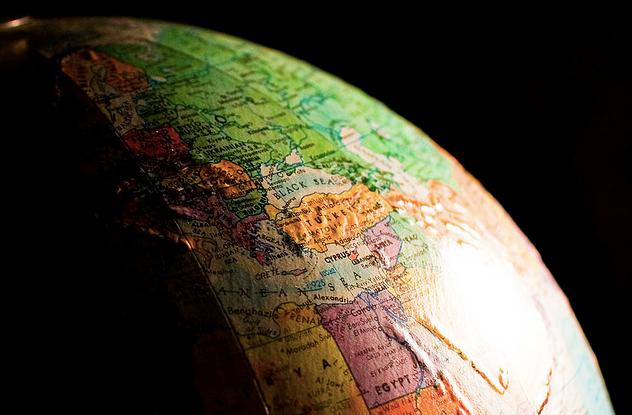 A light shining on an old globe of the world with a stark, black background.