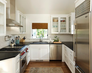 small kitchen with many wooden cabinets in white