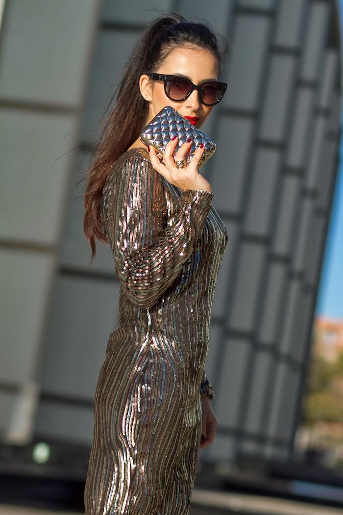 Clutch metálico acolchado de Victoria Delef con vestido dorado de lentejuelas para la Noche de Fin de Año