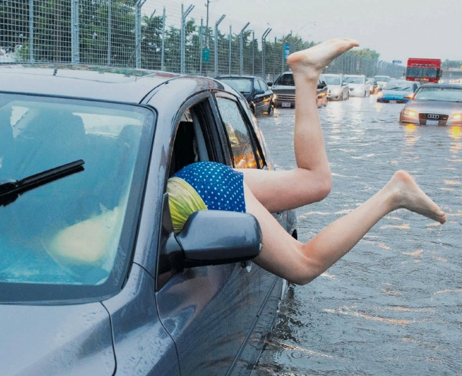 A woman climbing into her car on the flooded Toronto Indy course in Lake Shore Boulevard on Monday. A severe thunderstorm caused flash floods in Canada's largest city, cutting power to at least 300,000 people, shutting down subways and forcing people to abandon their cars on flooded highways.