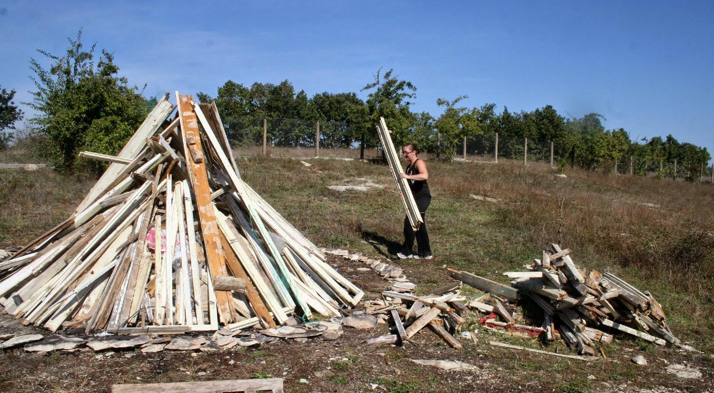 A loading super heavy wood onto the bonfire