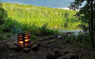 Fogata en el bosque muy cerca del lago de aguas claras
