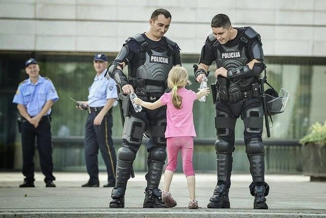 Девочка протягивает две бутылки воды полицейским в Боснии, 2013 год.