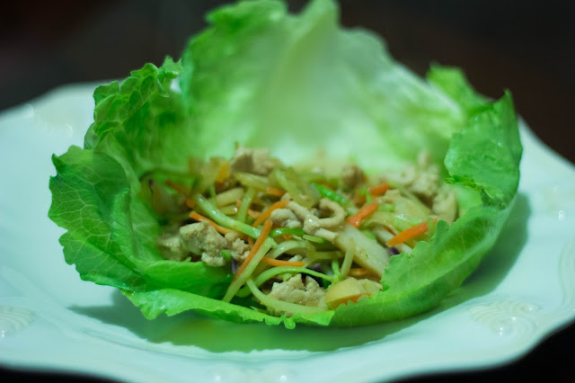 Plate with a turkey and vegetable stir fry on a lettuce leaf.