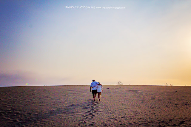 foto prewedding pasangan sedang berjalan menjauh di hamparan pasir