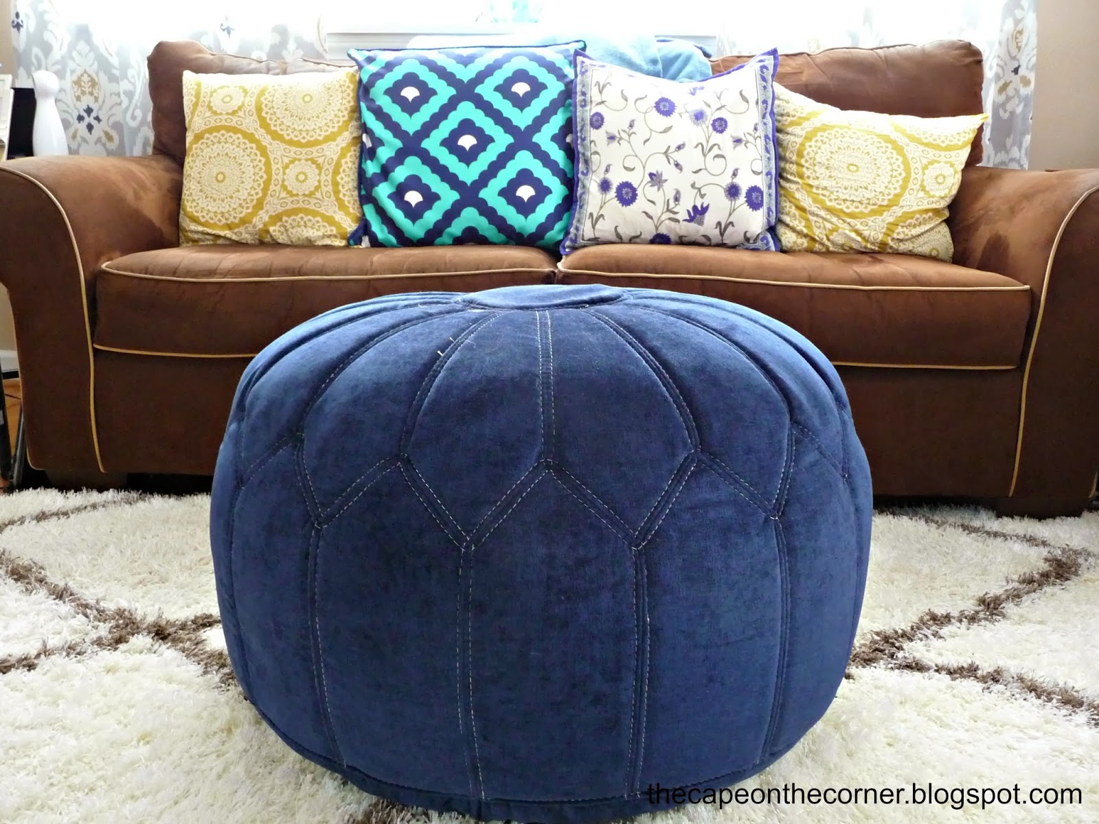 brown couch, blue poof, gold pillow