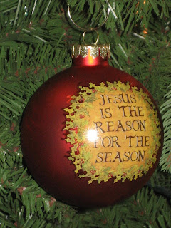 Giant Red bauble decorated in Christmas tree labeled with Jesus is the reason for the season letters photo