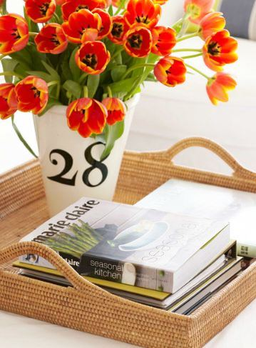 books, tulip flower arrangement in a white vase in a wicker serving tray